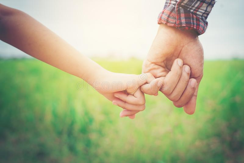 Chiuda su del padre che tiene la sua mano della figlia, così dolce, Ti della famiglia fotografia stock libera da diritti