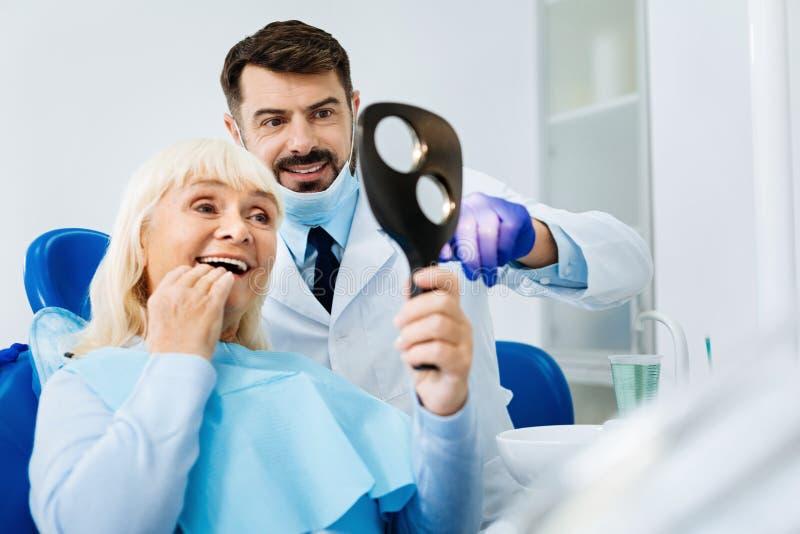 Chiuda su del paziente soddisfatto in ufficio dentario fotografia stock libera da diritti