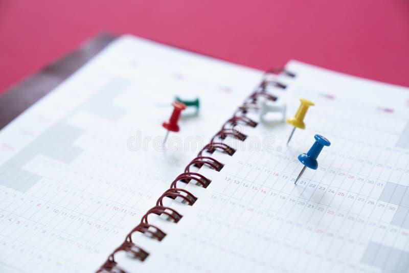Chiuda su del perno sul calendario sui precedenti rossi fotografie stock libere da diritti