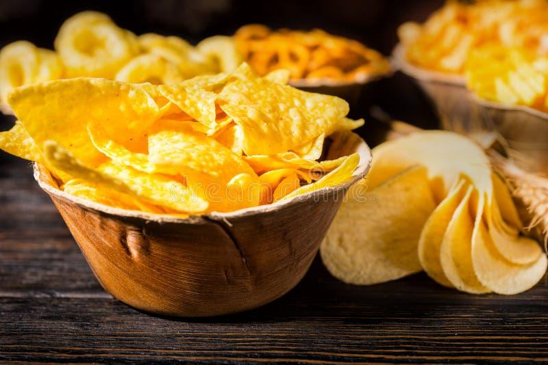Chiuda su del piatto di legno con i chip di tortiglia saporiti vicino alla p di legno fotografia stock