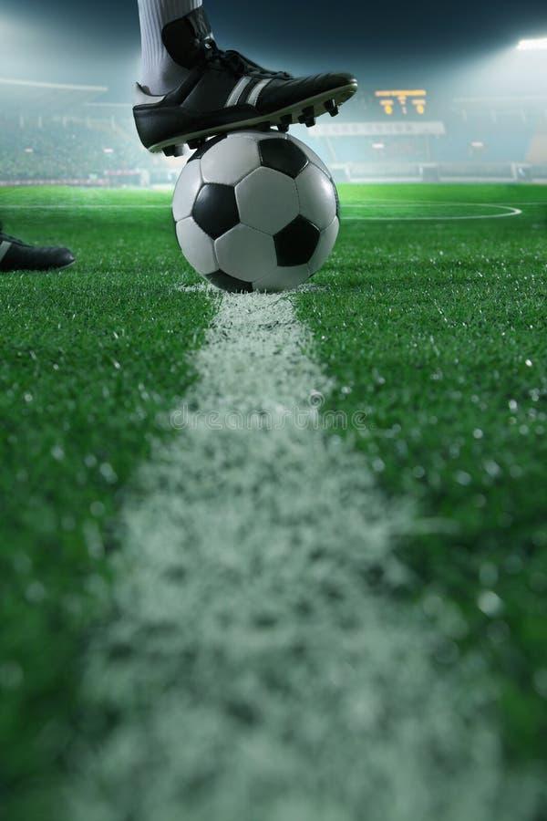 Chiuda su del piede sopra pallone da calcio sulla linea, la vista laterale, stadio fotografie stock