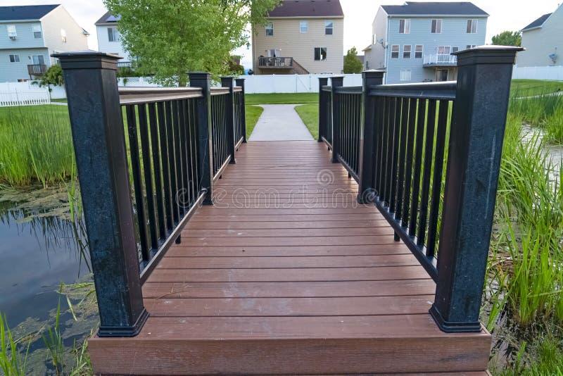 Chiuda su del ponte con la piattaforma di legno marrone e della guardavia nera sopra uno stagno erboso fotografia stock libera da diritti