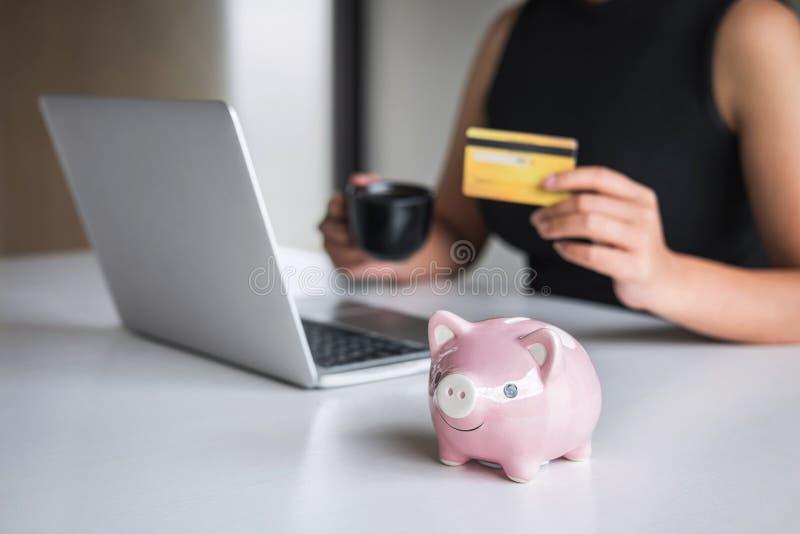 Chiuda su del porcellino salvadanaio, consumatore di donna di affari che tiene la carta di credito e scrivendo sul computer porta fotografie stock libere da diritti