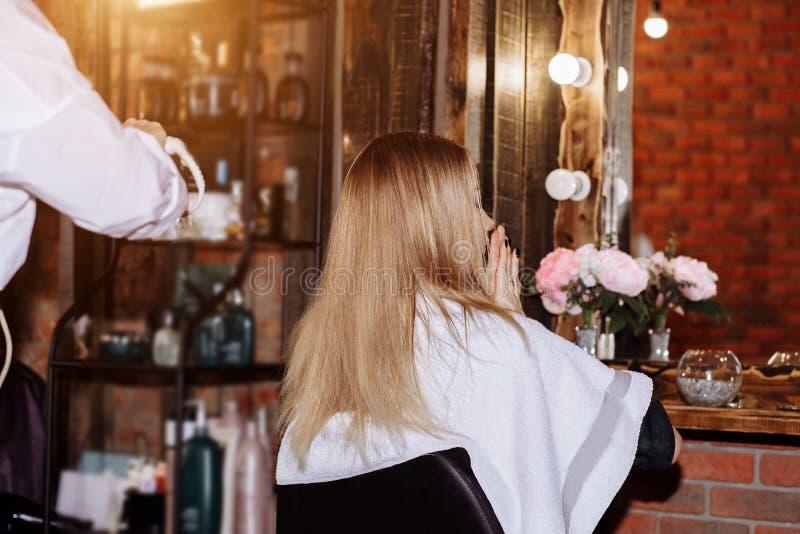 Chiuda su del processo che raddrizza i capelli biondi lunghi con i ferri dei capelli Bellezza, acconciatura, designazione calda,  fotografie stock