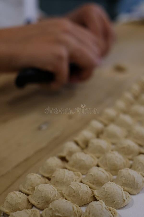 Chiuda su del processo della pastificazione La donna fa il orecchiette, pasta auriforme, tradizionale alla regione della Puglia d immagini stock