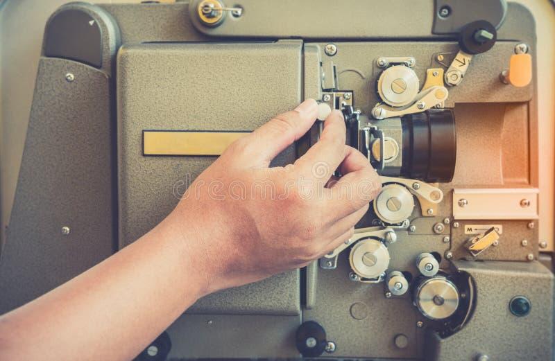 Chiuda su del proiettore di film mobile classico d'annata di 16mm o di 8mm con la mano e lo stile d'annata di colore fotografia stock
