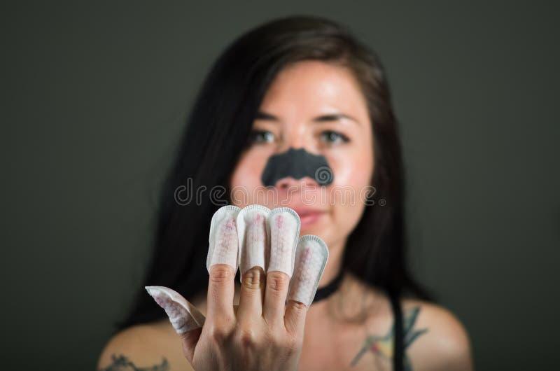 Chiuda su del protettore d'uso dei chiodi della giovane donna nei suoi chiodi ed in una maschera del naso per liberare la pelle d fotografie stock libere da diritti
