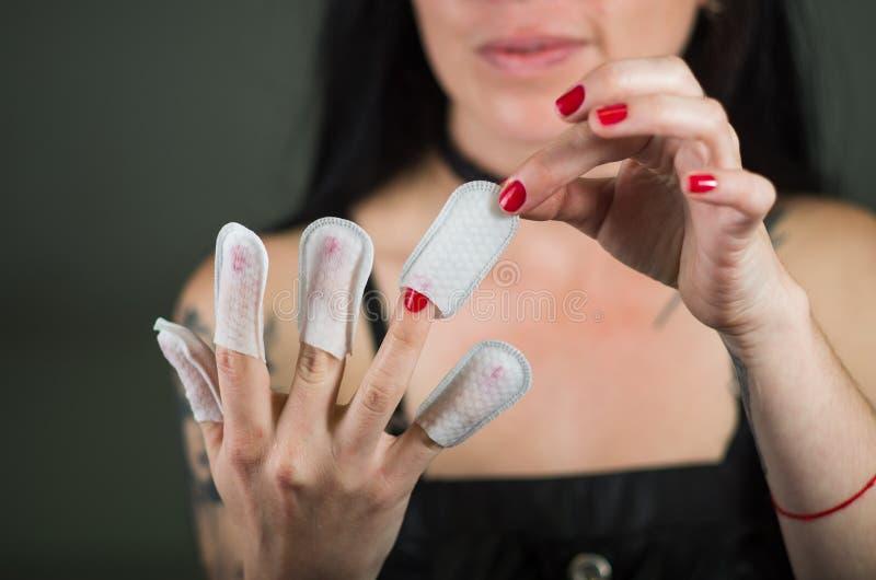 Chiuda su del protettore d'uso delle unghie della giovane donna nelle sue unghie, mano e manicure pulito ideale, in un fondo nero immagini stock libere da diritti
