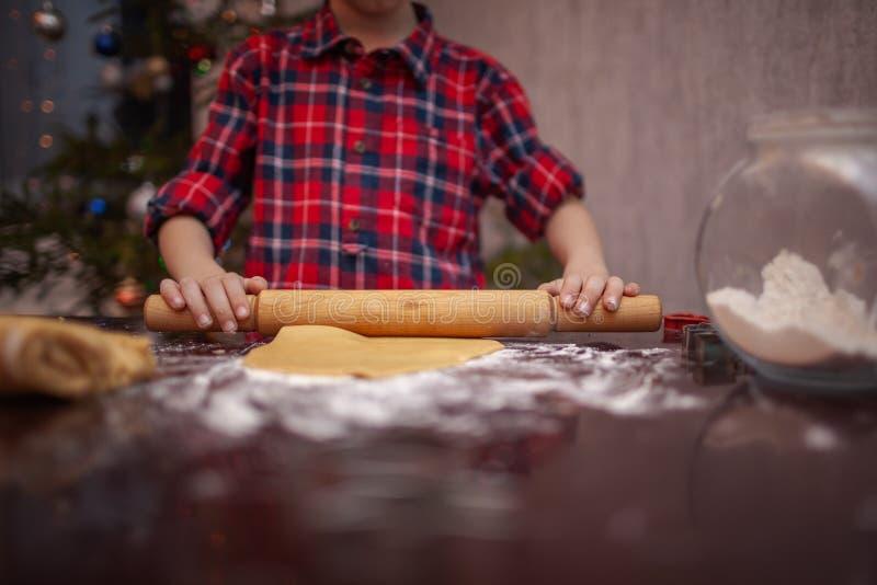 Chiuda su del ragazzo bollente dei biscotti del bambino nella cucina di Natale fotografia stock