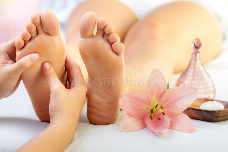 Chiuda su del reflexologist che massaggia i piedi femminili con olio aromatico in stazione termale fotografia stock
