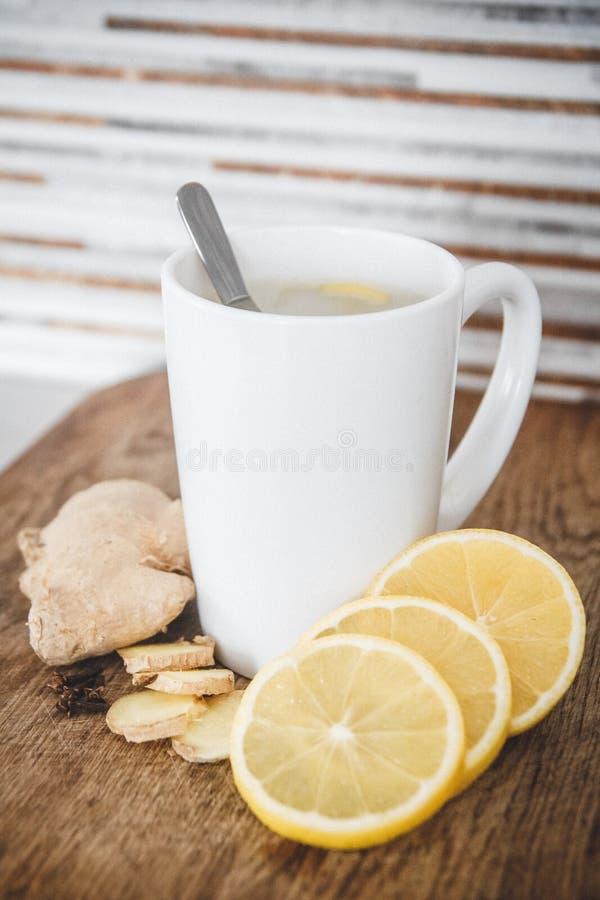 Chiuda su del tè caldo dello zenzero sulla tavola di legno fotografia stock