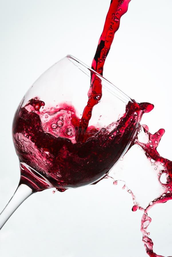 Chiuda su del versamento con la caduta di vino rosso fotografia stock