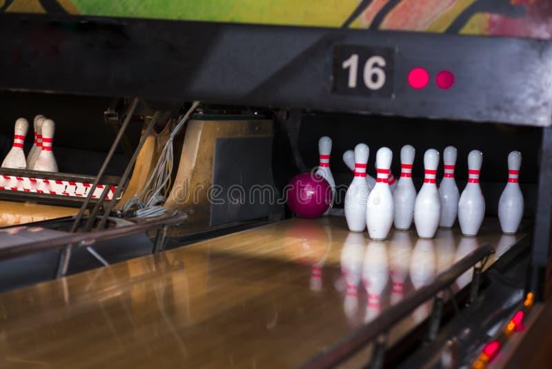 Chiuda su del vicolo al club di bowling fondo del vicolo di bowling del perno Un primo piano di una fila di dieci perni su una pa fotografia stock libera da diritti