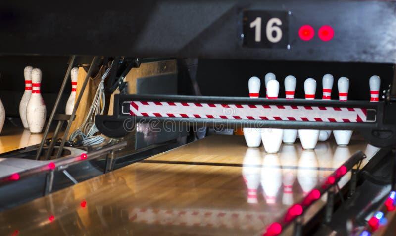 Chiuda su del vicolo al club di bowling fondo del vicolo di bowling del perno Un primo piano di una fila di dieci perni su una pa illustrazione di stock