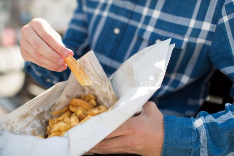 Chiuda su dell'adolescente che mangia le patate fritte che si siedono sul banco fuori fotografie stock libere da diritti