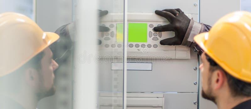 Chiuda su dell'apparecchiatura elettrica di comando di tensione di prova dell'ingegnere di manutenzione fotografia stock