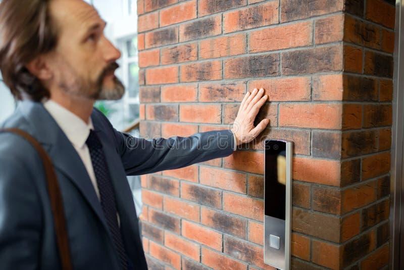 Chiuda su dell'ascensore aspettante dell'uomo d'affari barbuto nell'ufficio fotografia stock