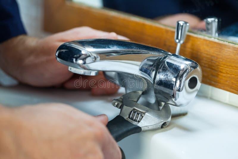 Chiuda su dell'idraulico che ripara il rubinetto fotografia stock