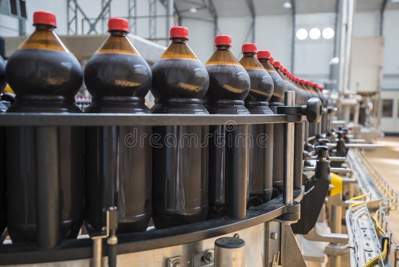 Chiuda su dell'industria di bottiglia di plastica su un nastro trasportatore immagini stock