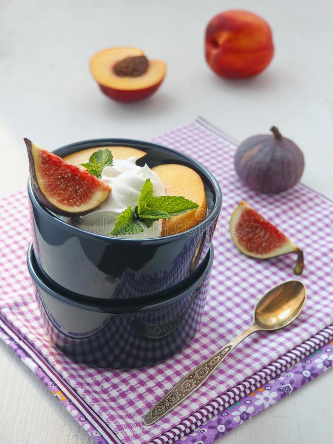 Chiuda in su dell'insalata di frutta Fichi freschi ed altri frutti di estate sopra la tavola di legno grigio chiaro immagini stock
