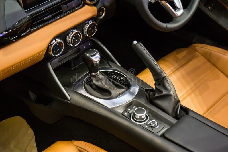 Chiuda su dell'interno di lusso moderno dell'automobile del dettaglio - volante, leva dello spostamento e cruscotto fotografia stock libera da diritti