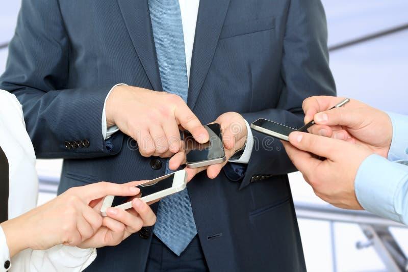 Chiuda su dell'la gente di affari che per mezzo degli Smart Phone mobili fotografia stock libera da diritti