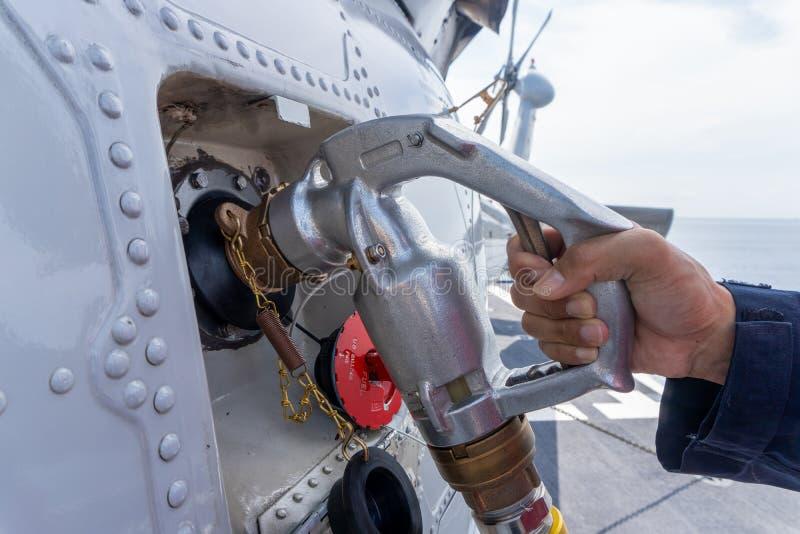 Chiuda su dell'operazione di rifornimento di carburante dell'elicottero a bordo della nave della marina militare fotografia stock libera da diritti