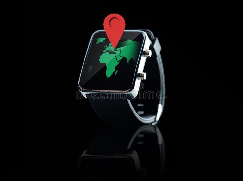 Chiuda su dell'orologio astuto con la proiezione cartografica del mondo immagine stock