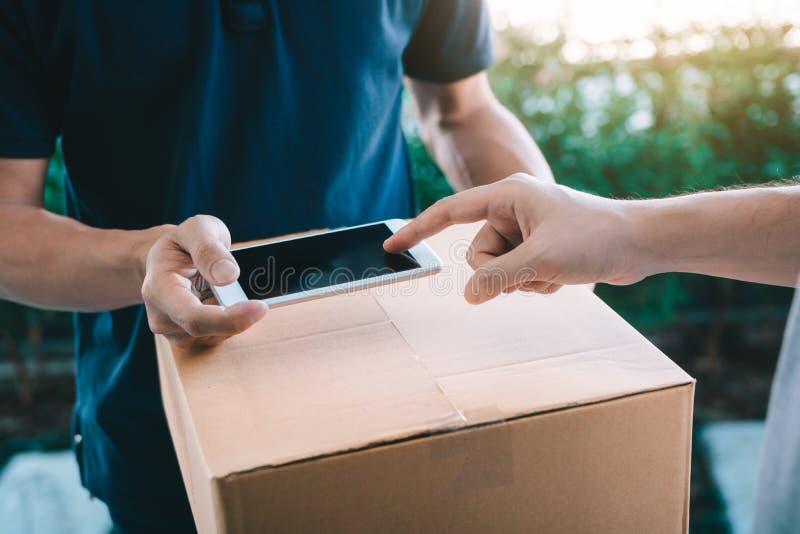 Chiuda su dell'uomo asiatico della mano facendo uso dello smartphone che preme lo schermo firmare per la consegna dal corriere a  fotografia stock