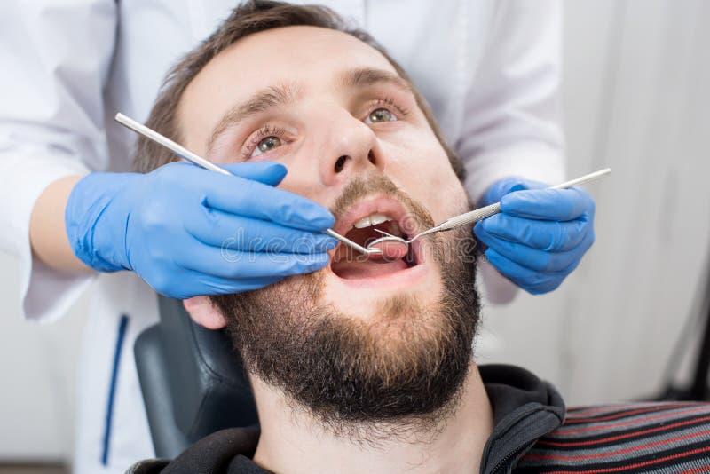 Chiuda su dell'uomo barbuto che ha controllo dentario su in clinica dentaria fotografie stock