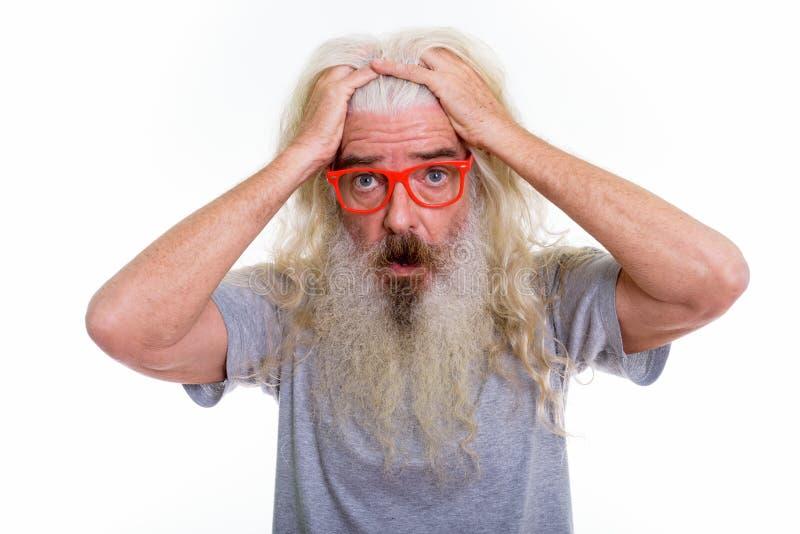 Chiuda su dell'uomo barbuto senior che pensa mentre sembrano i wi colpiti immagine stock