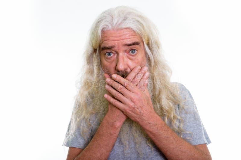 Chiuda su dell'uomo barbuto senior che sembra colpito mentre riguardano il Mo fotografia stock libera da diritti