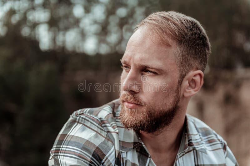 Chiuda su dell'uomo bionda-dai capelli barbuto bello che ritiene piuttosto serio fotografia stock libera da diritti