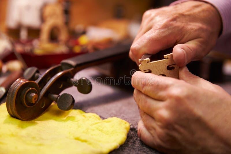 Chiuda su dell'uomo che ristabilisce il violino in officina fotografia stock