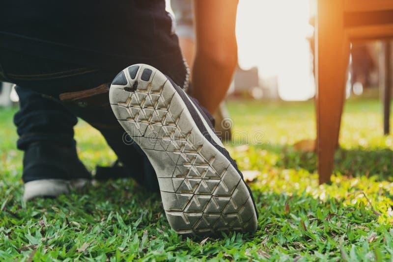 Chiuda su dell'uomo che scarpe da corsa d'uso in parco prima di pronto ad iniziare ed andare Concetto di sport e di affari La gen fotografie stock