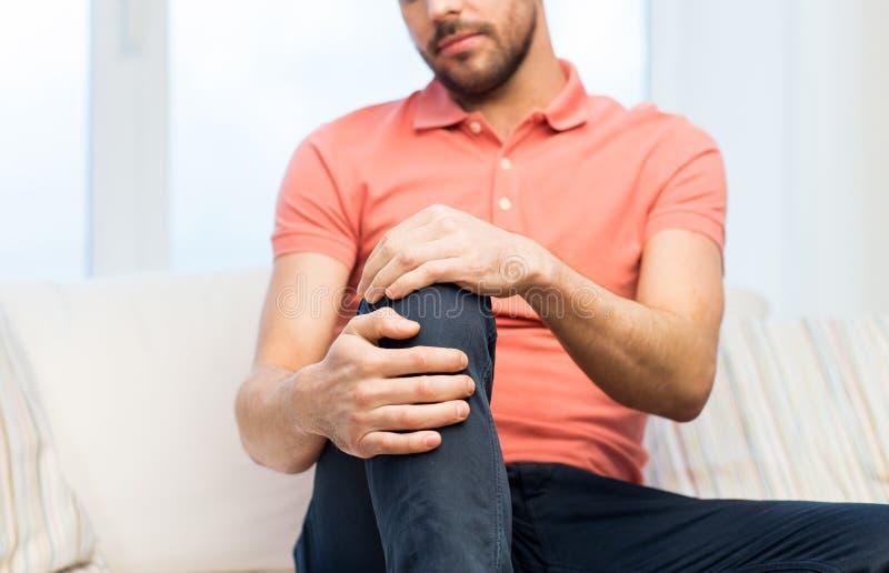 Chiuda su dell'uomo che soffre dal dolore in gamba a casa fotografia stock libera da diritti