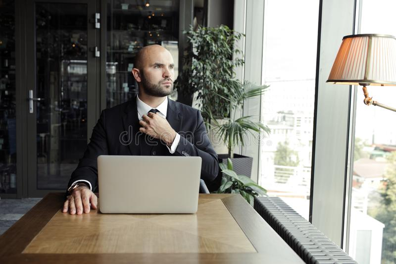 Chiuda su dell'uomo d'affari bello, lavorando al computer portatile in ristorante fotografie stock