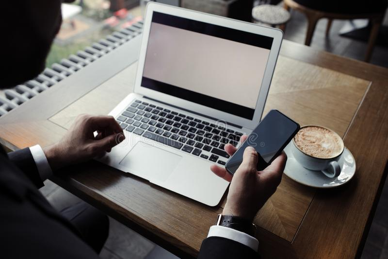 Chiuda su dell'uomo d'affari bello, lavorando al computer portatile in ristorante fotografia stock libera da diritti