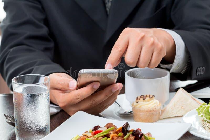 Chiuda su dell'uomo d'affari che controlla le notizie dal telefono cellulare fotografia stock libera da diritti