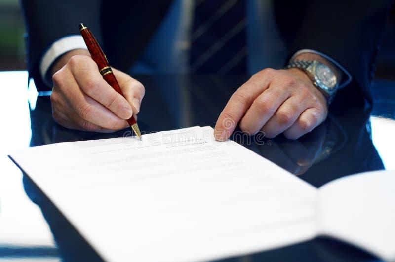 Chiuda su dell'uomo d'affari che firma un contratto. fotografie stock libere da diritti