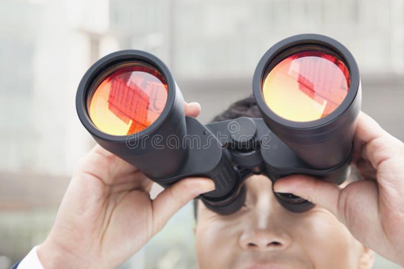 Chiuda su dell'uomo d'affari che guarda tramite il binocolo, la riflessione rossa nel vetro immagine stock