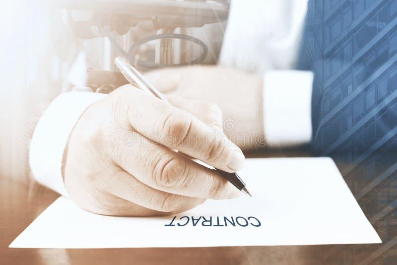 Chiuda su dell'uomo d'affari che si siede alla tavola ed al documento di firma immagini stock libere da diritti