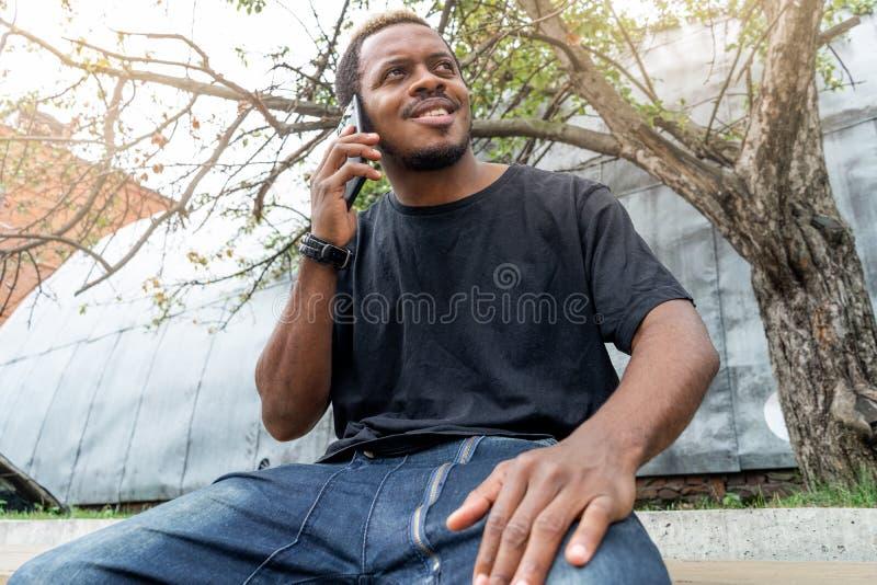 Chiuda su dell'uomo dalla carnagione scura in maglietta nera che parla dal telefono cellulare fotografia stock