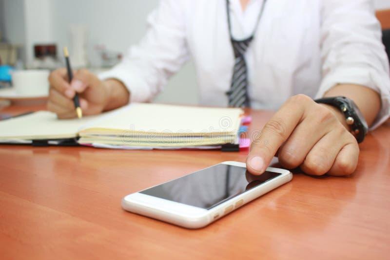 Chiuda su dell'uomo facendo uso dello Smart Phone mobile e di lavorare alla tavola in ufficio immagini stock libere da diritti