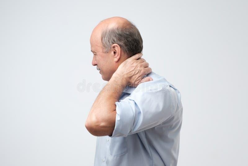 Chiuda su dell'uomo maturo in camicia blu con gli occhi chiusi che toccano il suo collo nel dolore immagine stock