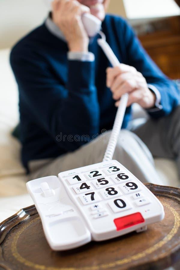 Chiuda su dell'uomo senior che per mezzo del telefono con la tastiera surdimensionata a fotografie stock