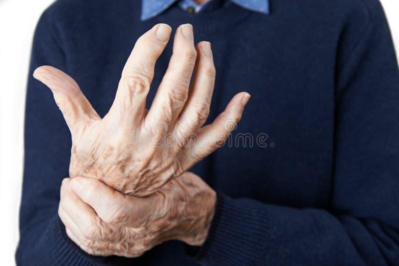 Chiuda su dell'uomo senior che soffre con l'artrite fotografia stock libera da diritti
