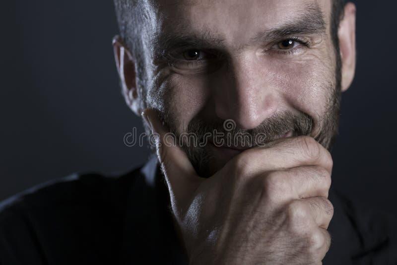 Chiuda su dell'uomo sorridente allegro con lo sguardo caldo immagine stock