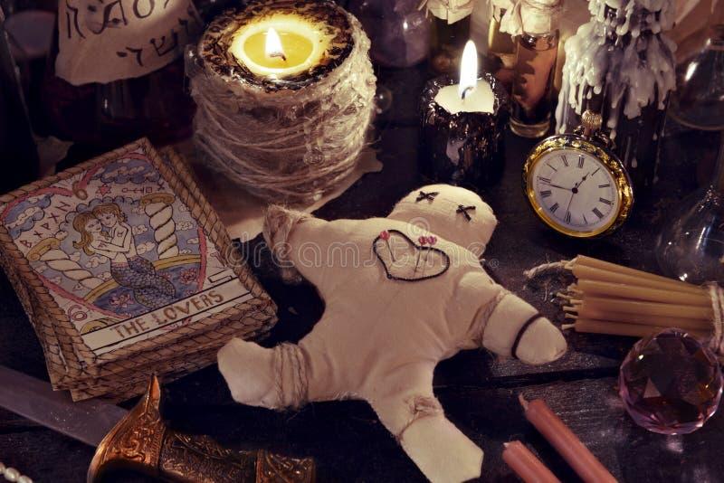 Chiuda su della bambola di woodoo, del coltello, delle candele brucianti e degli oggetti magici immagini stock libere da diritti