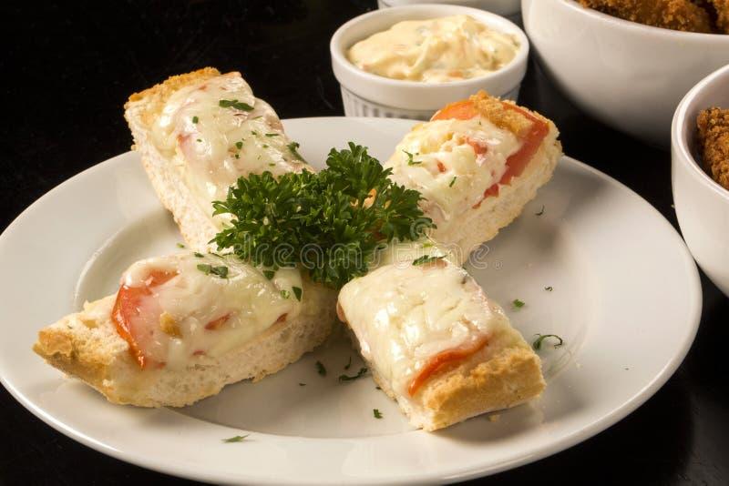 Chiuda su della Bruschetta con formaggio ed i pomodori fusi su di legno immagini stock libere da diritti